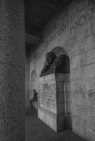 A homeless man sits next to the Rhodes Memorial quote.