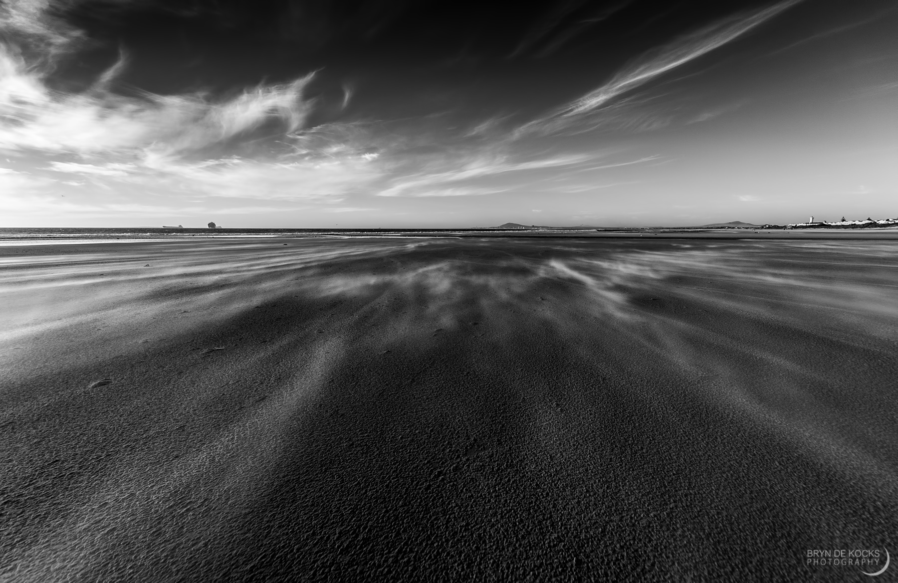 Cirrus clouds and sand blown across beach